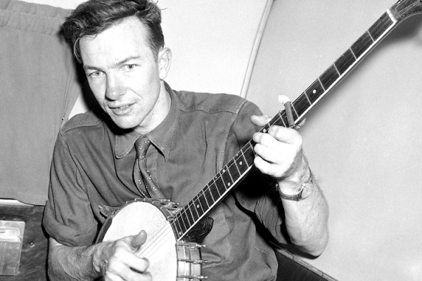 Henry A. Wallace, making a political tour of the American South, listens to Pete Seeger, a banjo-playing singer, on a plane between Norfolk and Richmond, Aug. 28, 1948. (AP Photo)